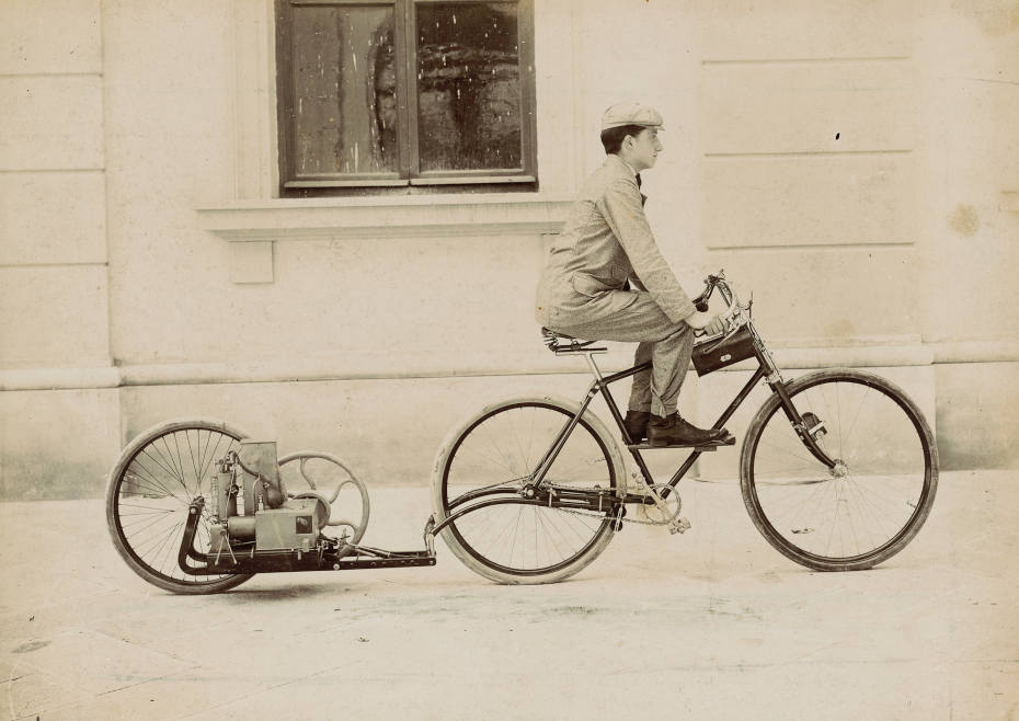 Photograph of Lauro Bernardi riding the motor-driven bicycle