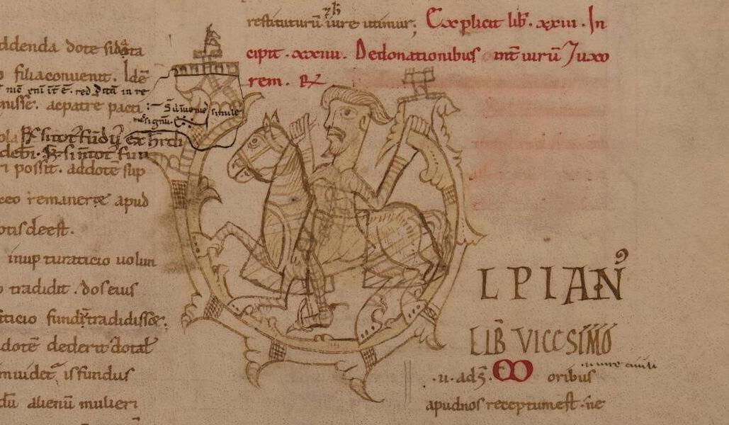 Capolettera del ms. 941, c. 193r. La U di Ulpianus è costituita da un tralcio fogliato ricurvo, al centro dl quale si staglia la figura di un cavaliere barbuto con cotta di maglia, su cavallo perfettamente bardato.